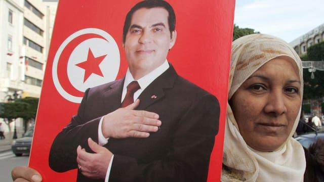 Eine Frau mit Kopftuch hält auf der Strasse ein Poster von Ben Ali in der Hand (Bild von 2009).