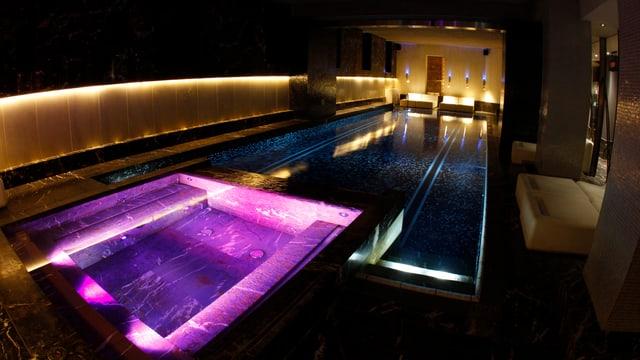 Ein bunt beleuchteter Swimming Pool in einem Hotel.
