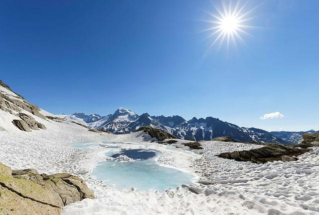 Blick auf einen Gletschersee unter blauem Himmel.