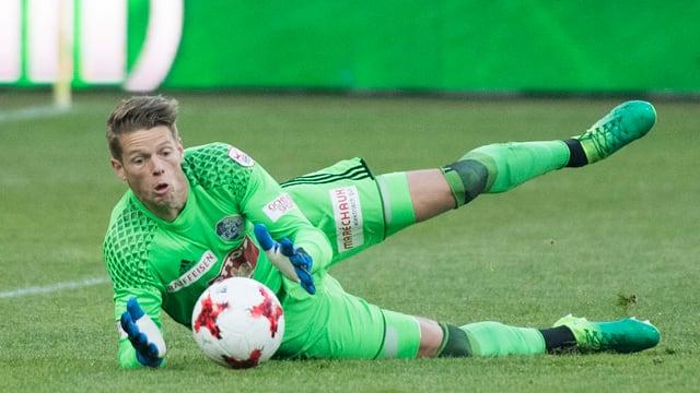 Goalie hechtet auf den Boden und fängt Ball mit beiden Händen.