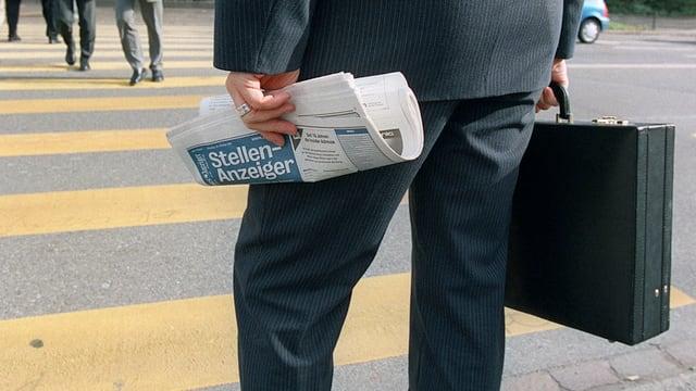 Ein Geschäftsmann hält einen Aktenkoffer und den Stellenanzeiger in der Hand.