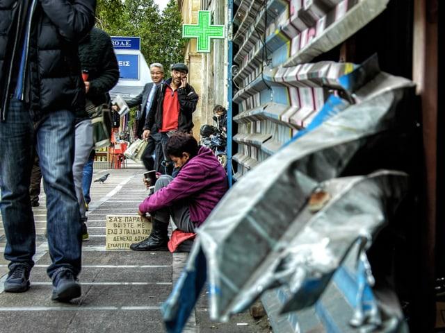 Eine Frau sitzt auf der Strasse, vor ihr steht ein Plakat.