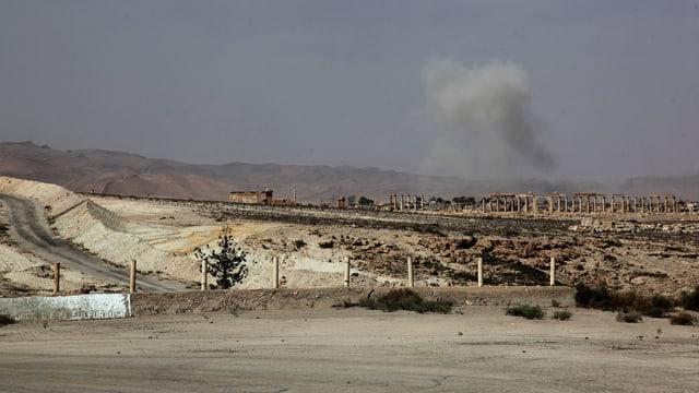 Nach einem Angriff mit Raketenwerfern steigt Rauch über der syrischen Stadt Palmyra auf