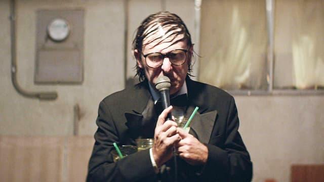 Ein Mann mit schütterem Haar, das fettig über der hohen Stirn klebt, schaut nach unten und spricht in ein Mikrofon.