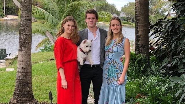 Zwei junge Frauen, ein junger Mann in der Mitte mit Hund auf dem Arm.