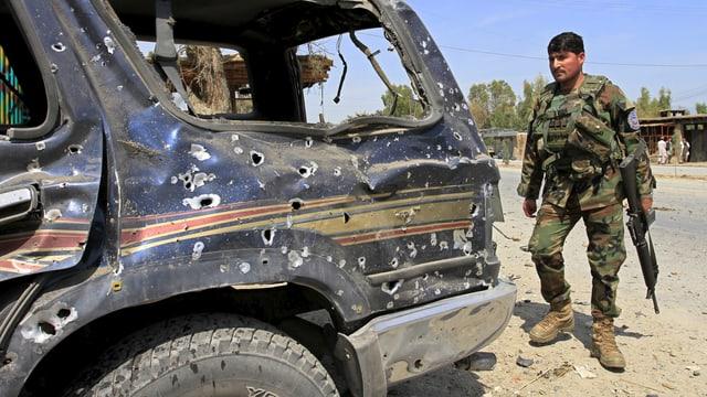 Ein afghanischer Soldat ohne Helm, mit Gewehr, steht hinter einem von Schüssen durchlöcherten Geländewagen.