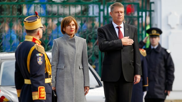 Iohannis steht neben seiner Frau, er hält die rechte Hand auf der Brust, im Bild auch ein Polizist sowie ein Angehöriger der Ehrengarde.