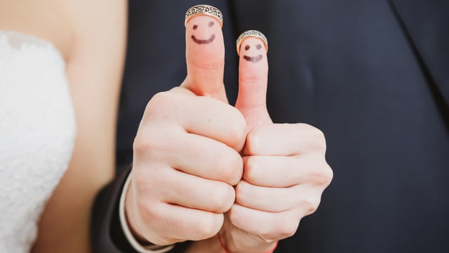 Brautpaar das Daumen mit aufgemalten Gesichtern hochhält.