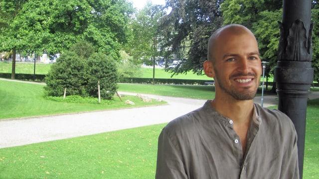 Ein Mann mit Glatze und kurzem Bart in einem Park.