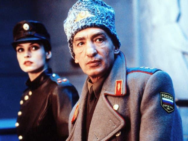 Ein Mann mit Fellmütze und Uniform steht neben einer Frau ebenfalls in Uniform.