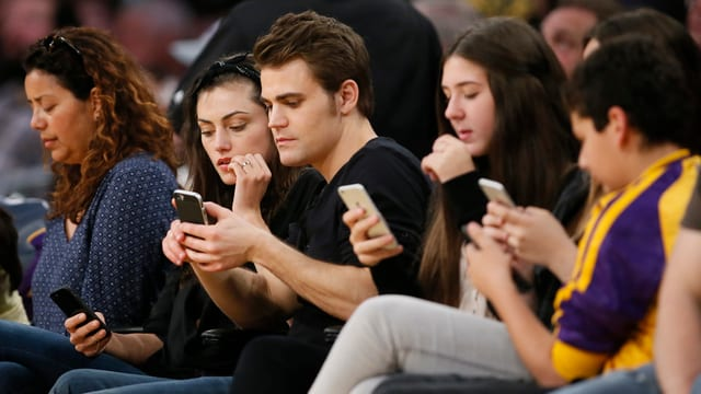 Junge Leute gucken auf ihr Smartphone.
