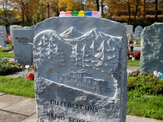 Ein Grabstein mit eingraviertem Zug, auf den ein Plastikzug abgestellt wurde.