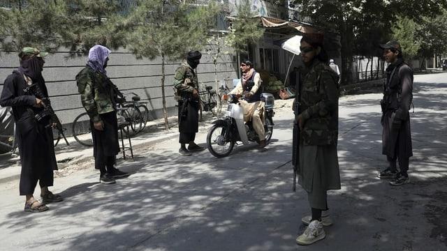 Bewaffnete Taliban lassen eine Motorradfahrer passieren