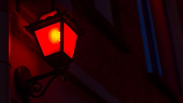 Eine rote Laterne an einer Hauswand.