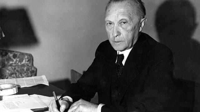 Konrad Adenauer, an einem Schreibstisch sitzend, mit Stift in der Hand, in die Kamera schauend.