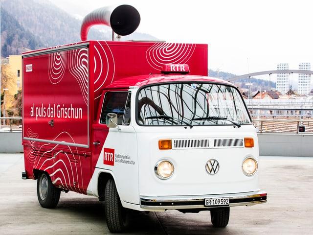 "In bus da VW (38 onns vegl) cun il corporate identiy design dad RTR ed il claim ""Al puls dal Grischun"". La part davos dal bus e bajegià enturn en stil da camiunetta. Sin il tetg è per lung in corn vid da metal."