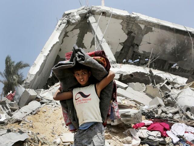 Palästinensischer Junge trägt Matratzen aus zerstörtem Haus