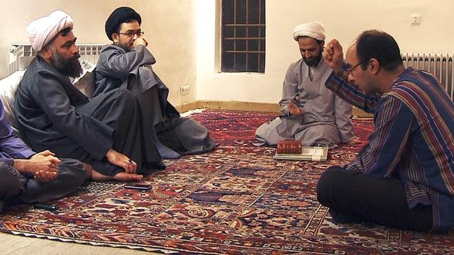 Vier Männer sitzen auf einem Teppich, drei tragen Turbane, einer gestikuliert.
