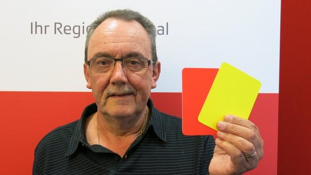 Porträt von Hans Waltert mit einer roten und einer gelben Karte in der Hand.