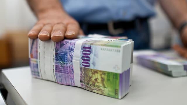 Ein Mann hält seine Hand auf ein Bündel 1000er Noten.