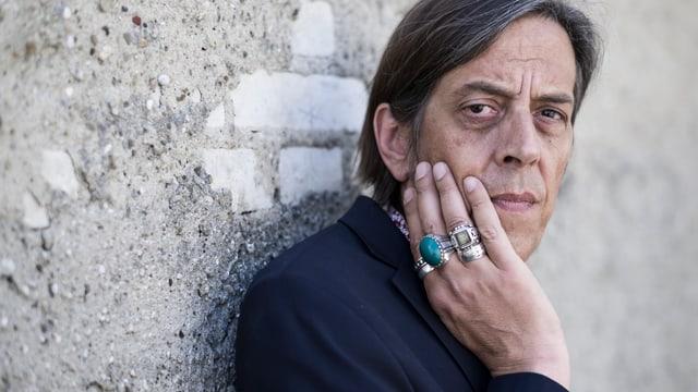 Pedro Lenz an einer Wand. Er trägt viele Fingerringe.