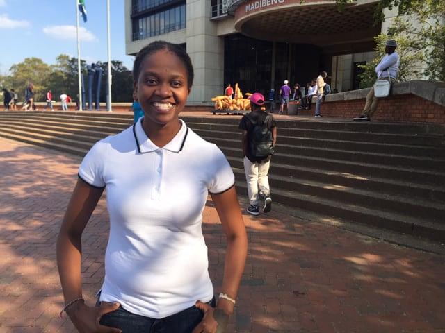 Studentin der Erziehungswissenschaften in weissem T-Shirt steht vor der Universität Johannesburg