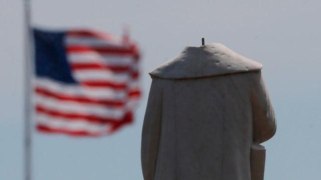 Statue ohne Kopf, im Hintergrund eine wehende US-Flagge.