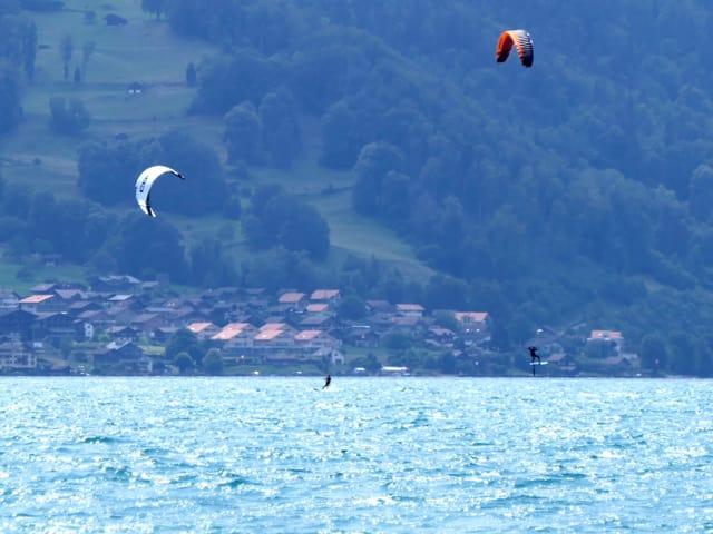 Zwei Kitesurfe lassen sich vom Wind über den See ziehen.