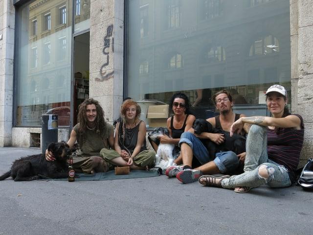 Fünf Menschen und drei Hunde sitzen auf der Strasse am Boden.
