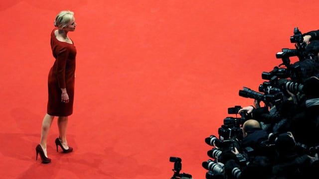 Eine Frau auf dem Roten Teppich. Vor ihr eine riesige Schar Fotografen.
