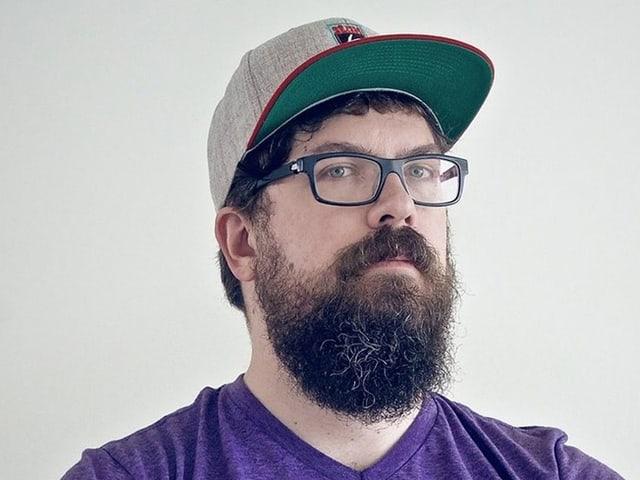Mann mit Bart, Brille und Baseball-Cap.