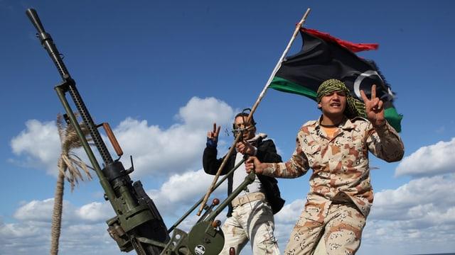 Zwei junge Männer in Tarnkleidung schauen in die Kamera und formen aus ihren Händen ein Peace-Zeichen. Über ihnen weht die Flagge Libyens, vor ihnen ist eine Waffe zu erkennen.