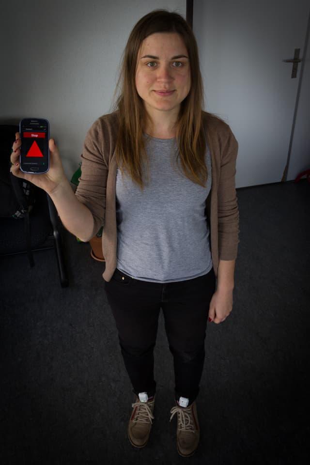 Eine junge Frau hält ein Smartphone in der Hand, an den Füssen sind Sensoren befestigt.