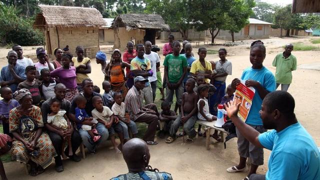 Mann erklärt Ebola-Prävention vor Dorfbewohnern