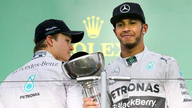 Nico Rosberg schielt mit dem Rücken zur Kamera auf den WM-Pokal, den Lewis Hamilton in den Händen hält.