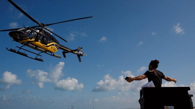 Ein Mann gestikuliert in Richtung eines Helikopters