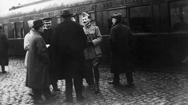Männer in Uniform und Zivilkleidern vor einem Zug stehend.