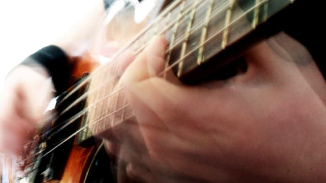 Verschwommenes Bild: Zwei Hände auf einem Bass.