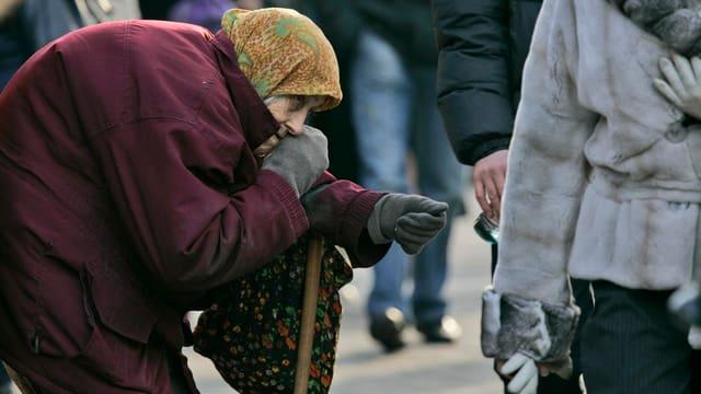 Alte Frau streckt ihre Hand für eine Spende aus.