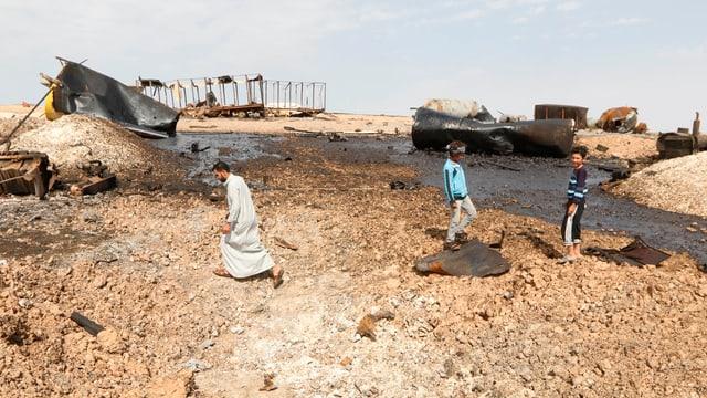 Zerstörte Tanks und eine grosse Öllache in einem wüstenähnlichen Gebiet, drei Personen sind auch im Bild.