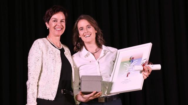 Monica Gschwind und Sabina Hafner auf der Bühne, Hafner hält sie Auszeichnung in den Händen.