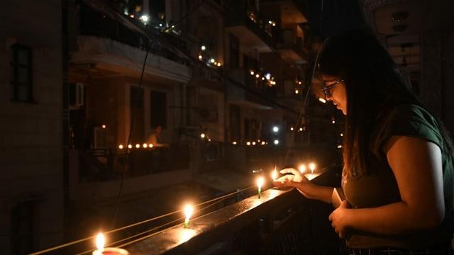 Eine Frau entzündet auf ihrem Balkon Kerzen.