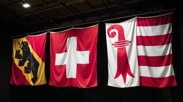 Drei Wappen-Fahnen hängen an einer Stange; Bern, die Schweizer Fahne und eine von Jura.