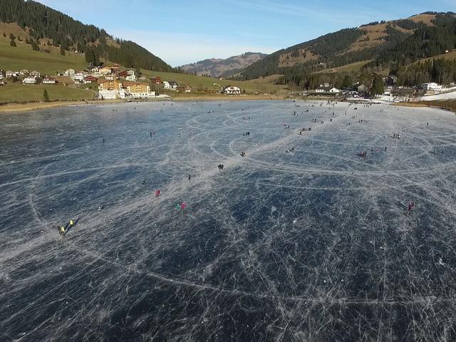 Gefrorener See mit Schlittschuhfahrern.