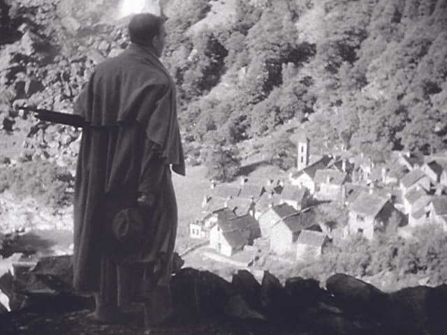 Filmszene in Schwarzweiss: EIn Man im Mantel schaut von einem BErg auf ein kleines Tessiner Dorf.