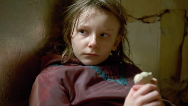 Ein kleines Mädchen mit verängstlichtem Blick ist an eine Wand angelehnt.