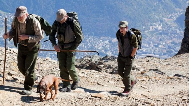Drei Jäger laufen mit Stock und Rucksack über einen steinigen Bergpfad. Dabei ist auch ein Hund.