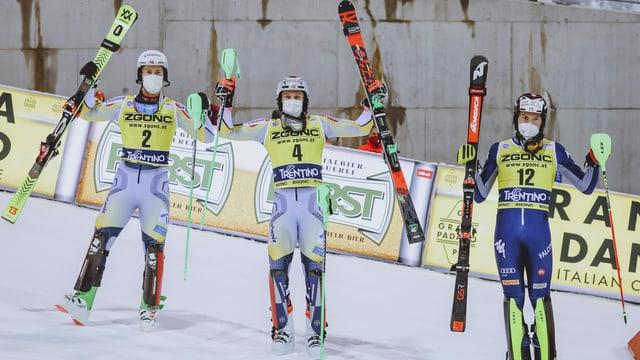 Trais skiunzs che tegnan ad aut lur skis e bastuns