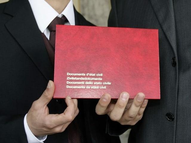 Pèrin mussa la cuverta cun ils documents dal stadi civil.