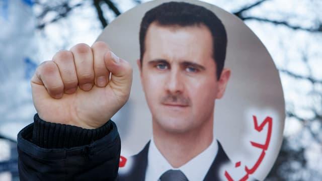 Eine ausgestreckte Faust ist vor einem Plakat mit Assad-Konterfei zu sehen.